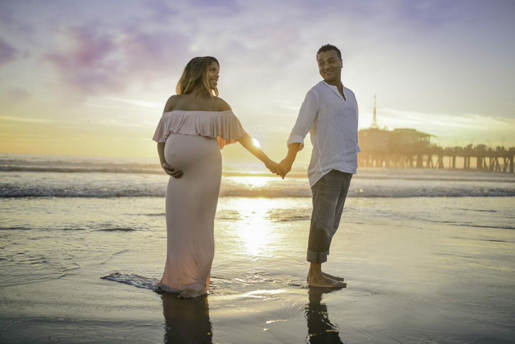 Pregnant mom holds hands with her partner as the sun sets on the Pacific Ocean by the Santa Monica Pier during a maternity photo-shoot with Artshaped Photography.