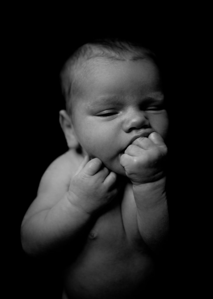 Black and white image of newborn baby sucking his left fist with eyes semi-closed. We only see his upper naked little body in this image captured by ArtShaped Photography and Birth services in Los Angeles, California.