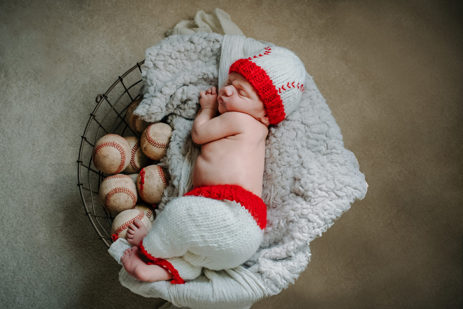 Newborn baby dressed up as baseball player asleep in a basket full of baseballs in occasion of his newborn photoshoot with ArtShaped Photography and Birth Services