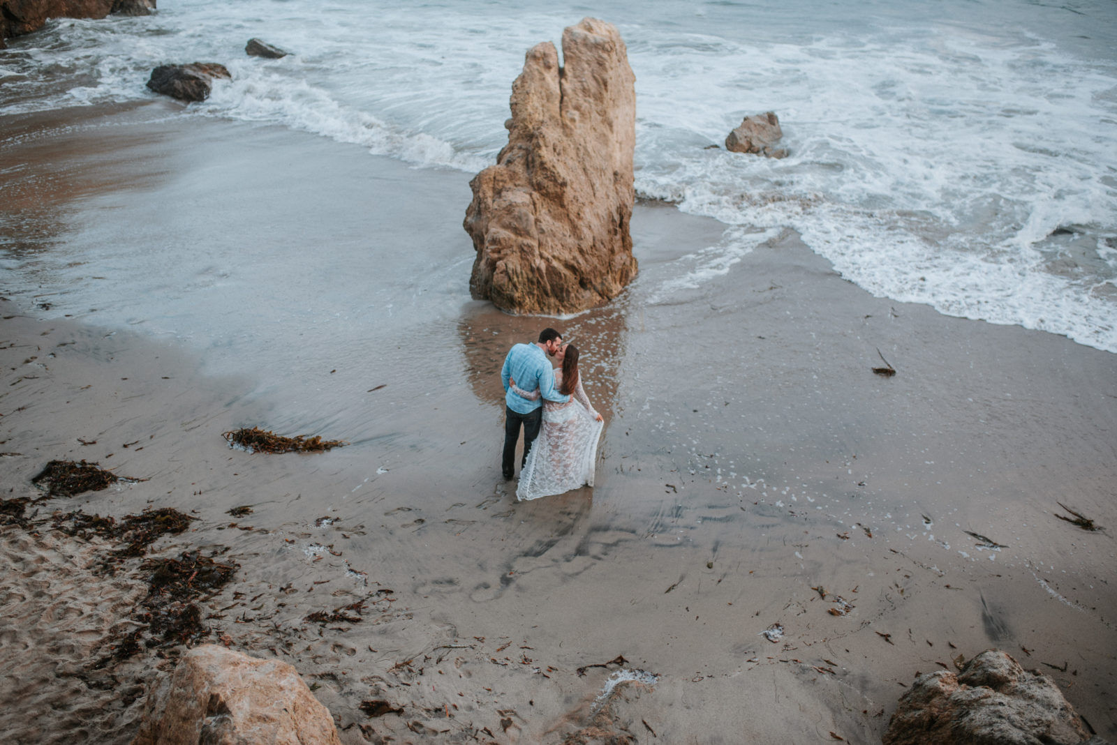 Color image overlooking El Matador State Beach in Malibu of pregnant mother hugging her partner in front of the waves, captured by ArtShaped Photography and Birth Services.