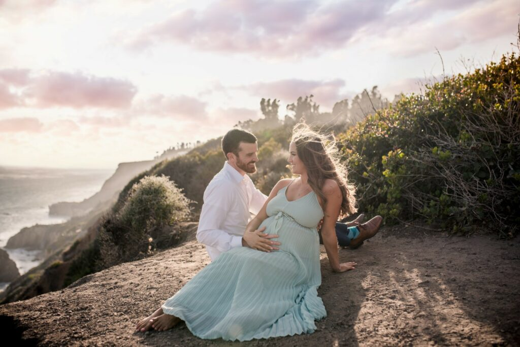 A pregnant couple look at each other while sitting on the cliff overlooking El Matador State Beach at sunset hour, photographed by ArtShaped Photography and Birth Services.