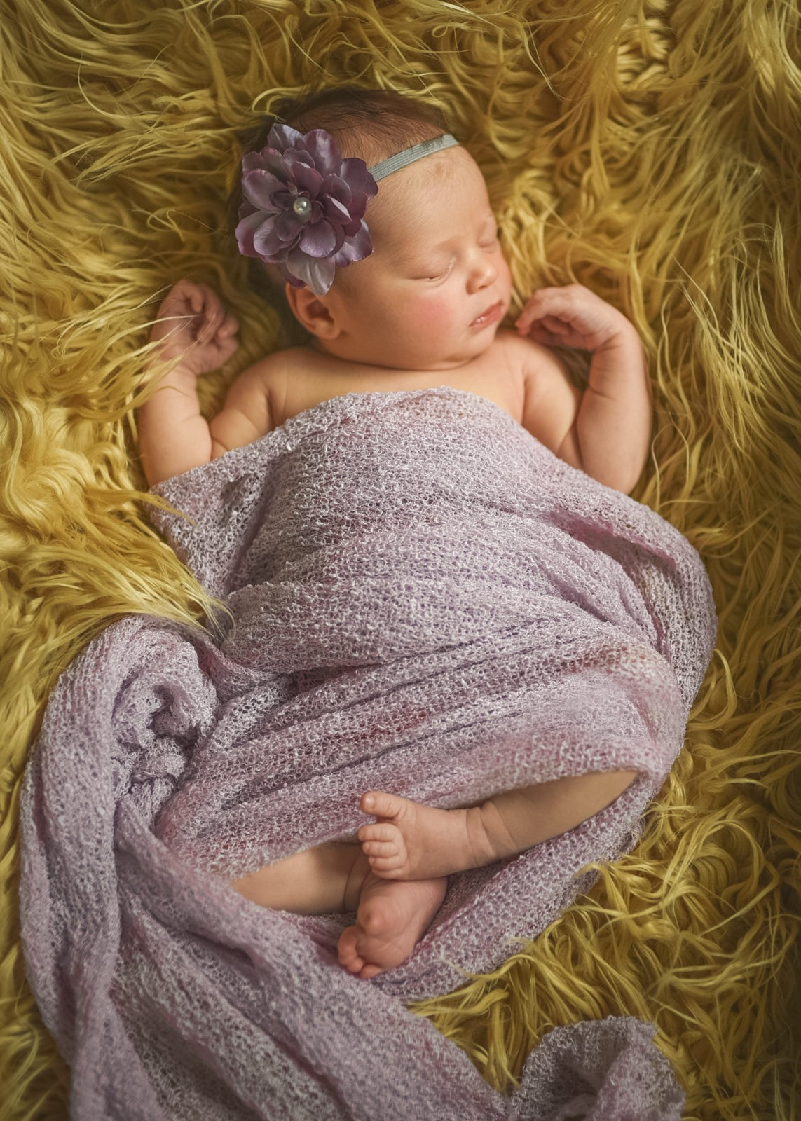 Newborn baby girl sleeps peacefully while laying on a furry blanket and soft swaddle during a photo session with Artshaped photography in Westwood, Los Angeles, Califronia.