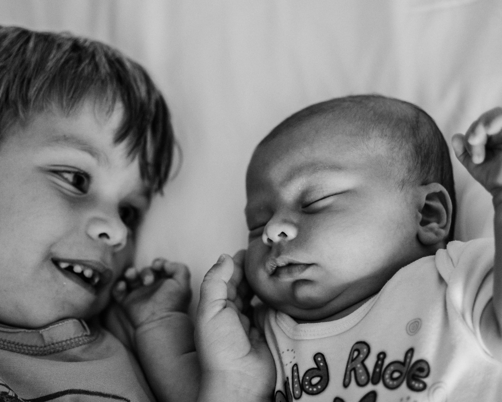 Top view of black and white photograph of big brother snuggling with his newborn baby brother while he touches the softness of his skin captured in Santa Monica during a family dcmentary session by Artshaped photography and Birth services.