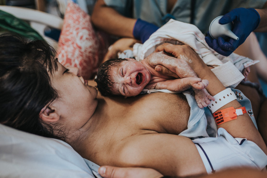 Baby's first cry in mom's arms seconds after birth. She is still covered in thick white vernix. Photo captured by ArtShaped Photography and Birth Services in Los Angeles CA.