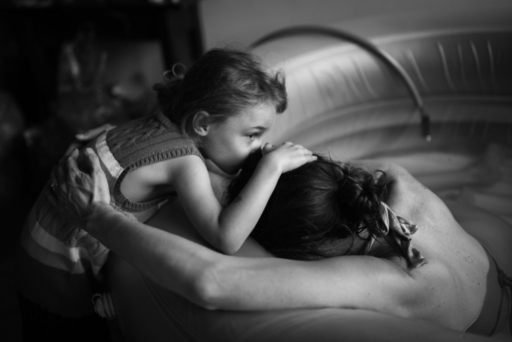 In this black and white image of birth, little daughter hugs and kisses her mom as she participate to the birth of her little sister, captured by Los Angeles based Artshaped photography