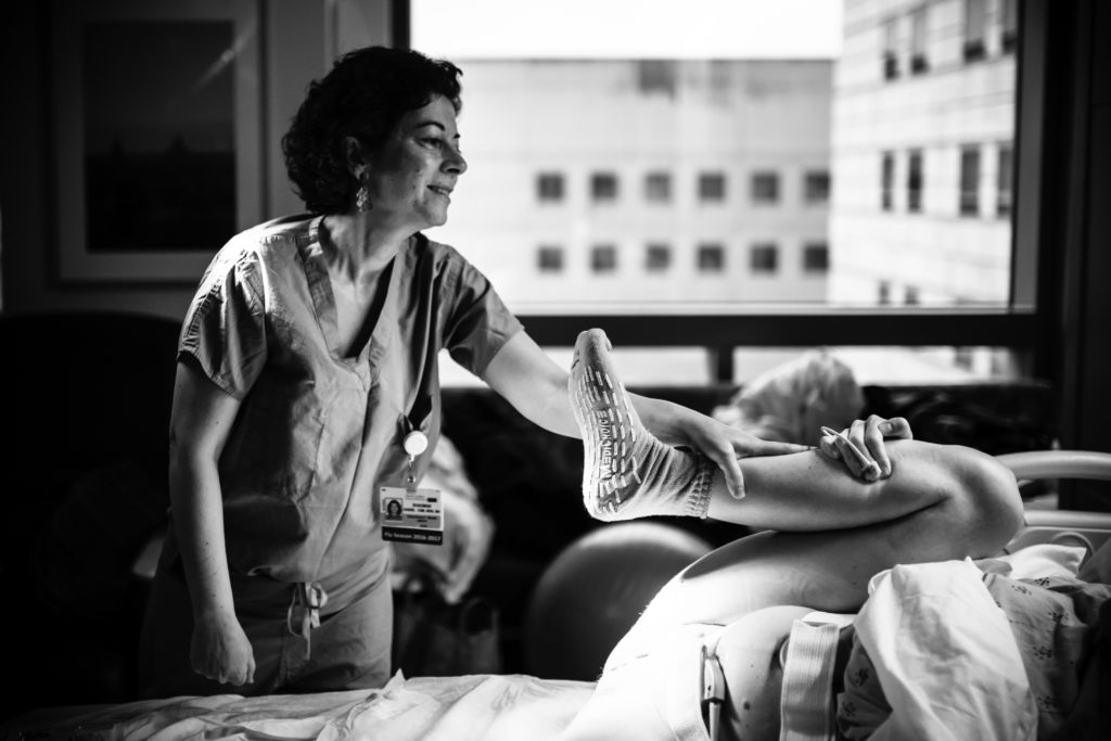 Black and white image of Midwife Shadman talking and supporting mom during pushing captured by Artshaped  birth photography in Los Angeles, California.