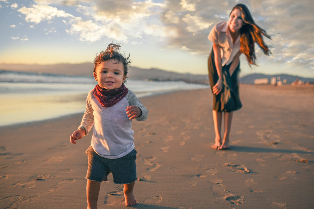 Mom and child play at the beach in this family portrait sunset session by Artshaped photography in Santa Monica, California