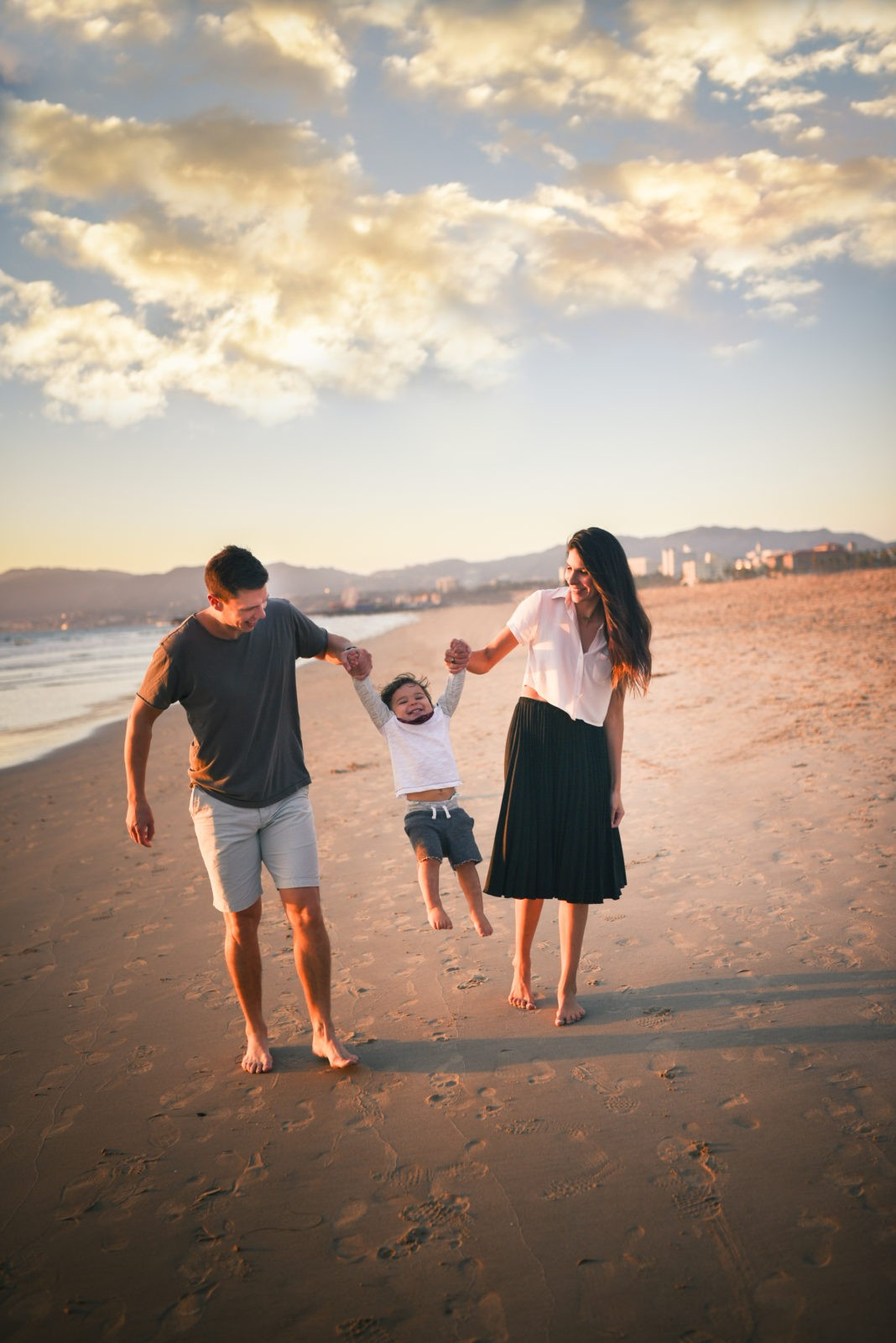 Mom and dad swing their son while walking barefeet on the sand of the Santa Monica shore during a sunset family photo session with Artshapedphotography.