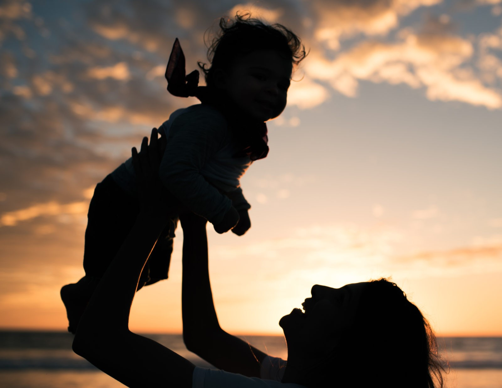 In this sunset family portrait by Artshaped photography in Santa Monica, California a young mother lifts her son in the sky agaist the clouds lit by the sun setting on the beach.