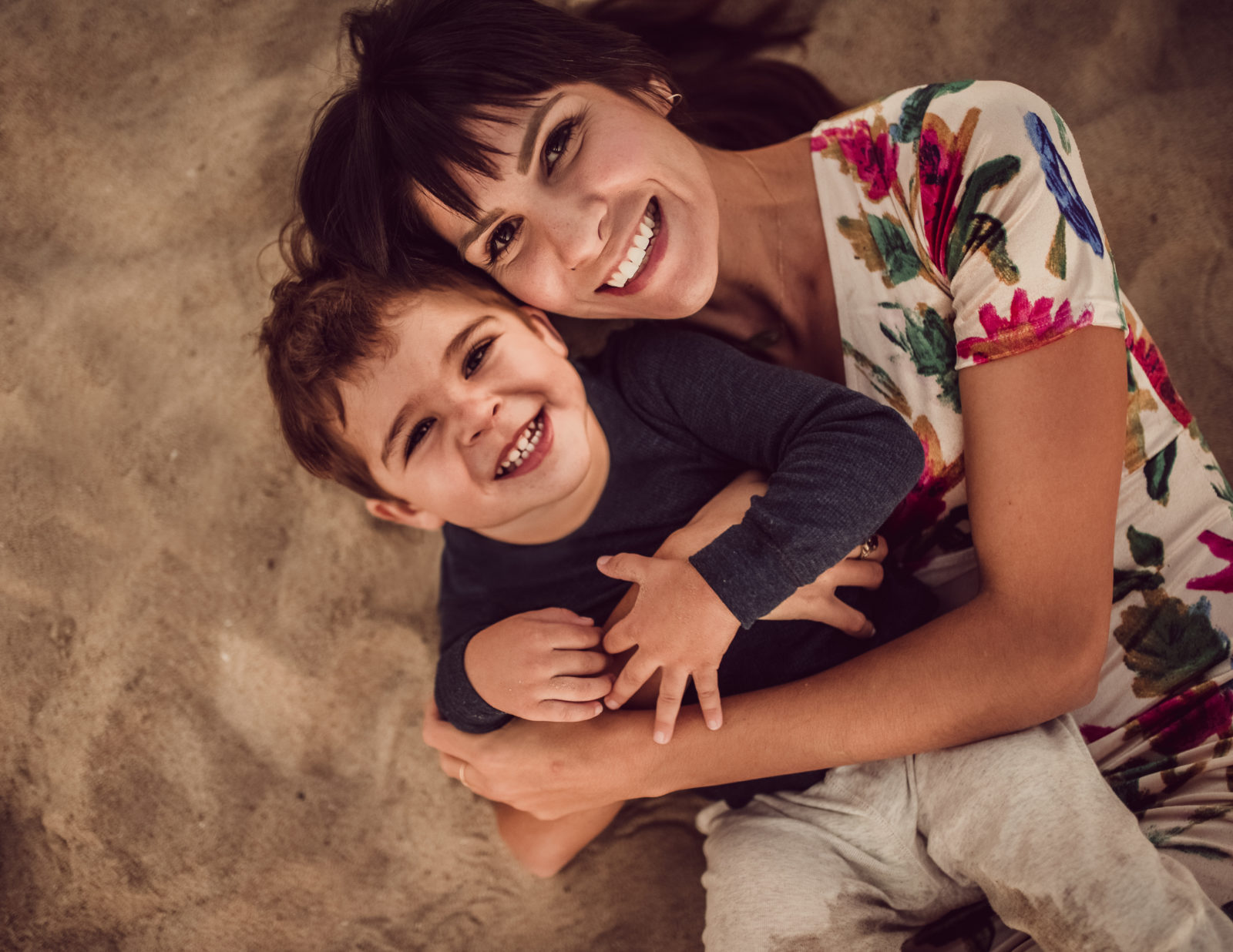 Mother and son captured from above by Artshaped photography while playing in the sand during their family photo session in Santa Monica, California.