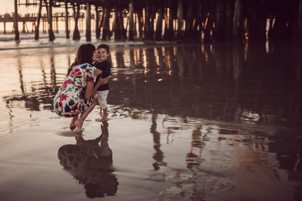 Mom and her little boy exchange sweet kisses during their family photo session by the Santa Monica Pier with Artshaped photography.