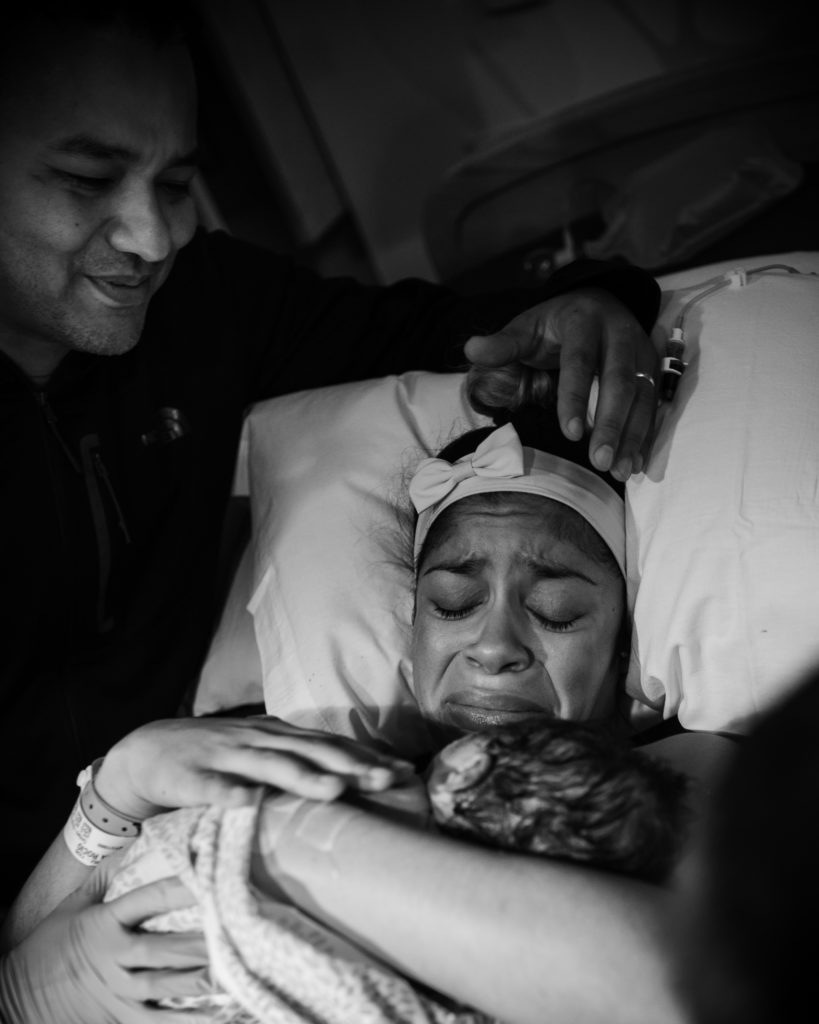 In this black and white photo, Artshaped photography captures the emotions of the first bond between mon and her baby, while dads looks over them with a loving smile,