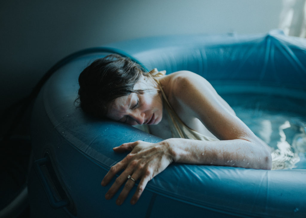 Mom breaths through the waves of labor while finding relief in the birth tub, in Venice CA and photographed by ArtShaped Photography and Birth Services.