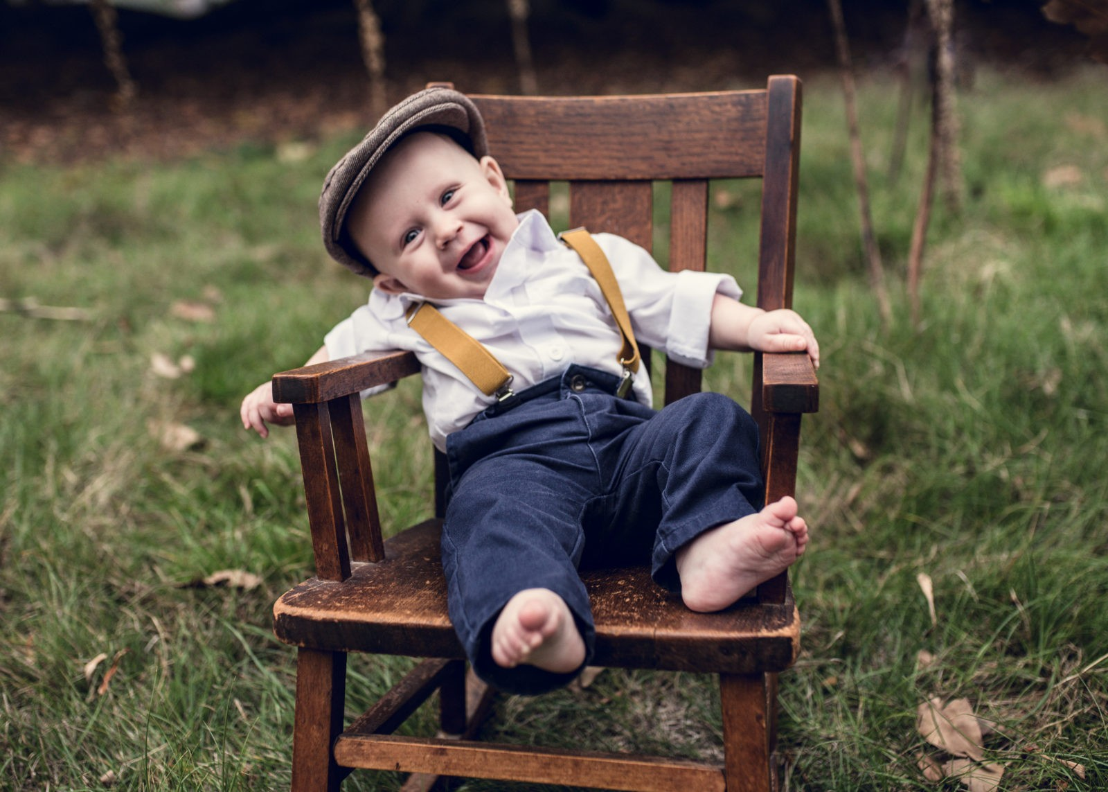 Close up photo of happy baby dressed up in suspenders and hat, smiling at the camera for ArtShaped Photography and Birth Services during his family photography session in Santa Monica