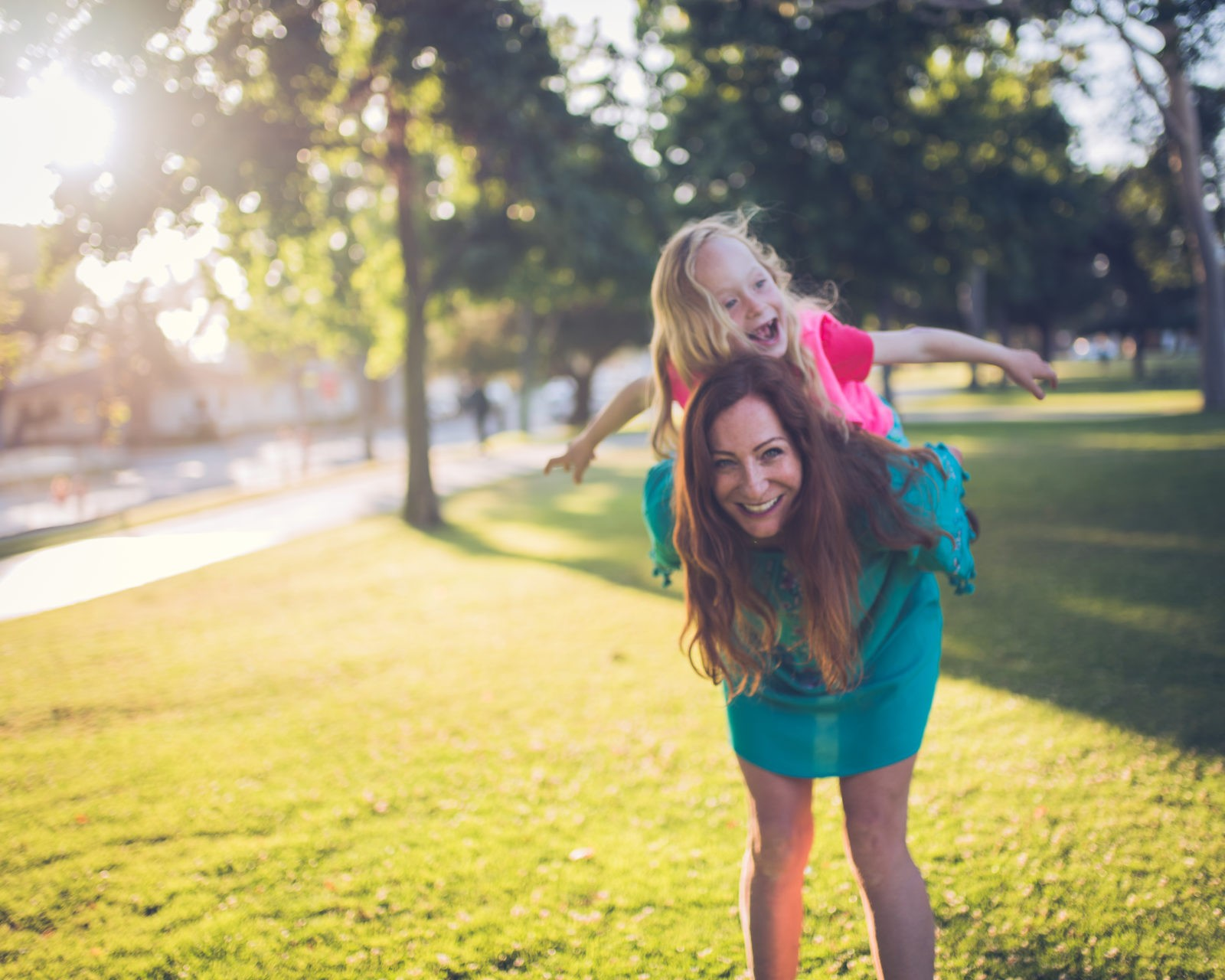 In this family photography session by Artshaped photography mother and daughter play piggy back at Clover Park in Santa Monica as the sun light filters through the trees.