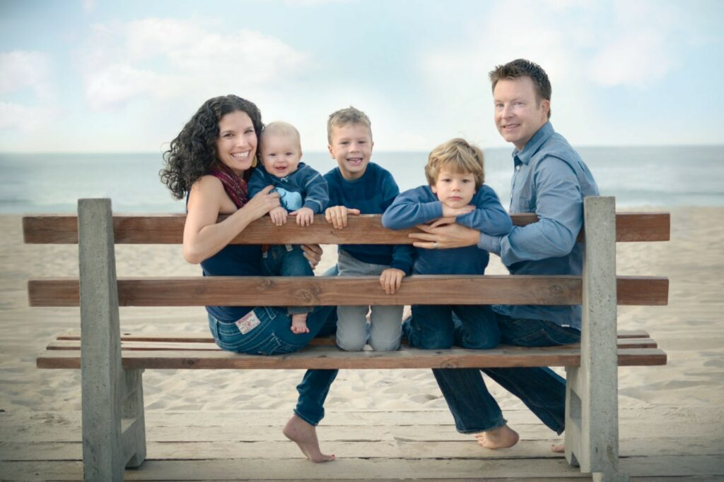 Mom, dad and their three boys pose sitting on a beanch at the beach for Los Angeles based Artshaped photography.