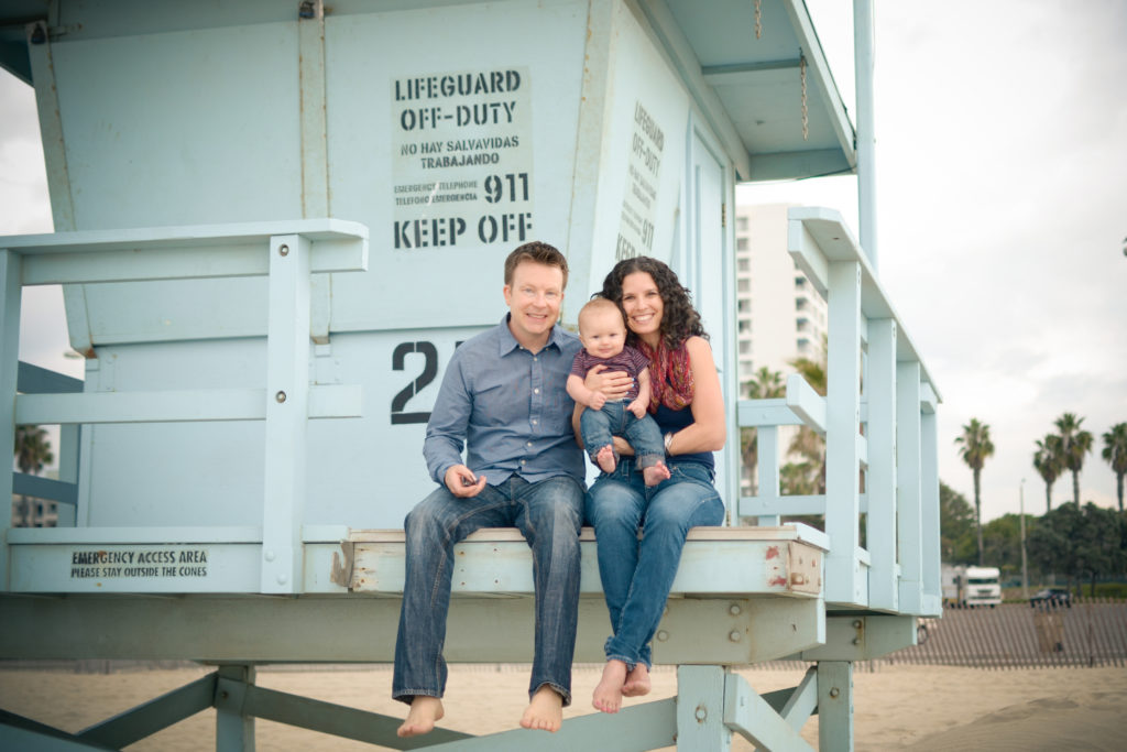 Mother and father pose with their baby boy on the lifeguard tower in Santa Monica, photographed by family photographer Diana Hinek of Artshaped photography.