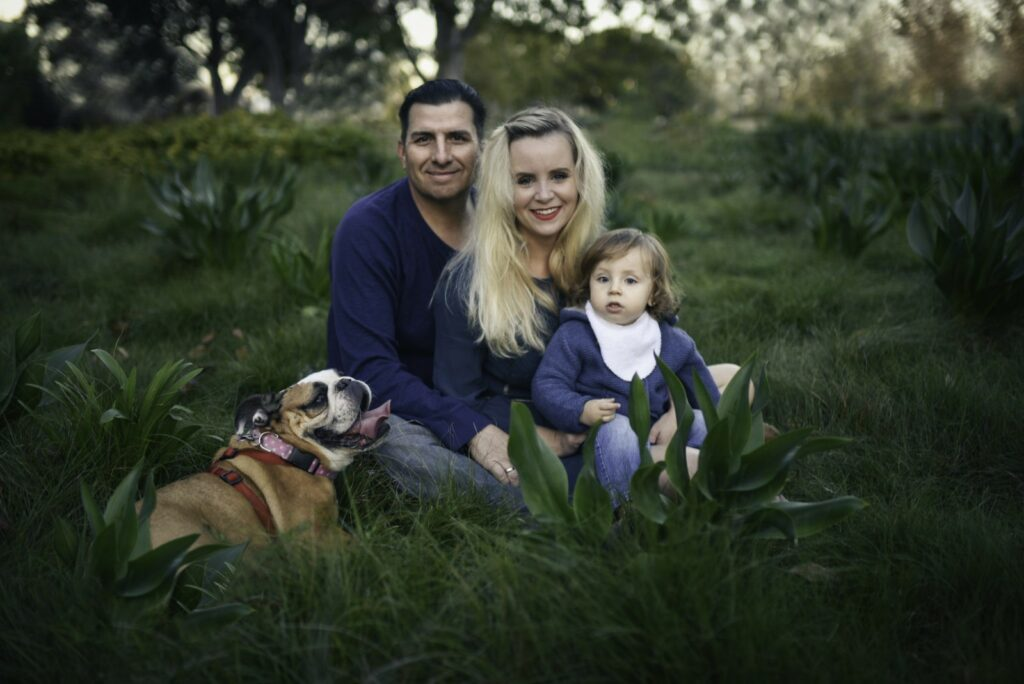 Colorful photograph of mom and dad with young child and dog sitting in the grass at Tongva Park in Santa Monica, California captured by Family photo session Artshaped photography
