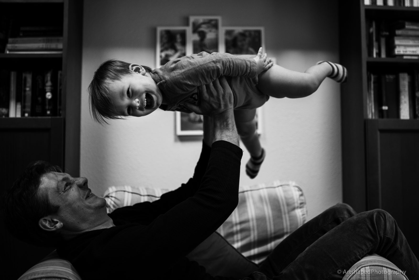 Black and white image of father holding his son in the air while he laughs and enjoys the ride looking at the camera of ArtShaped Photography and Birth Services in Santa Monica, CA.