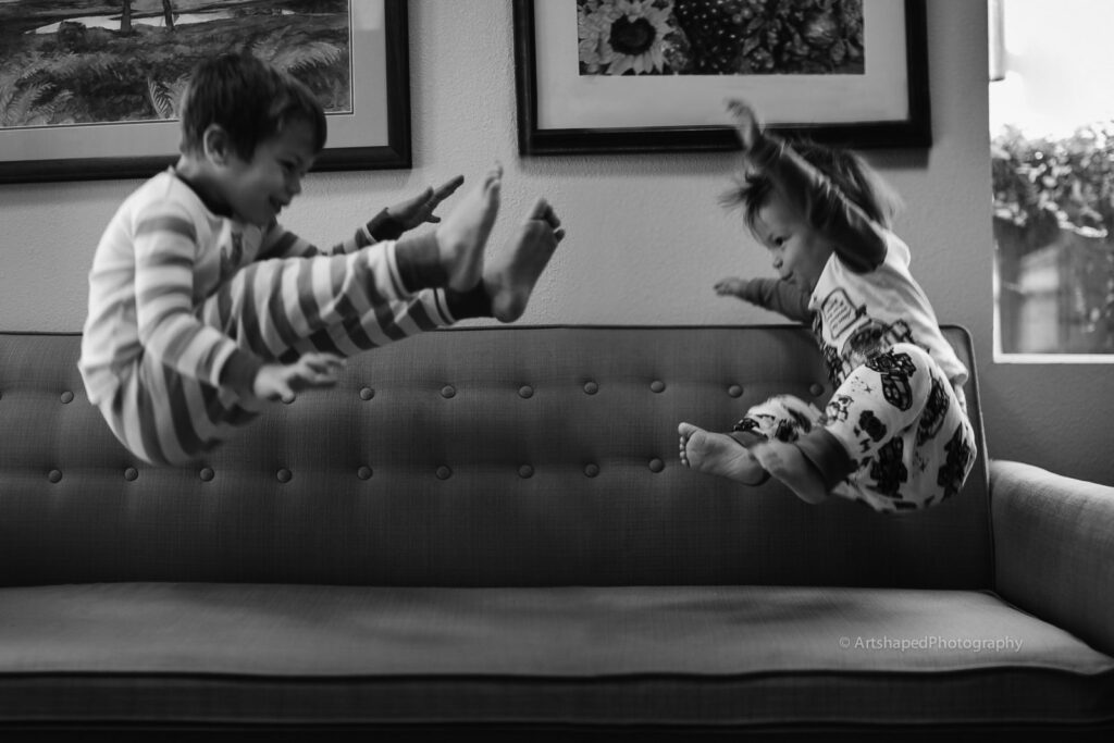 Black and white image by ArtShaped Photography and Birth Services of two children wearing pjs and kicking their legs up in the air as the jump on their couch.