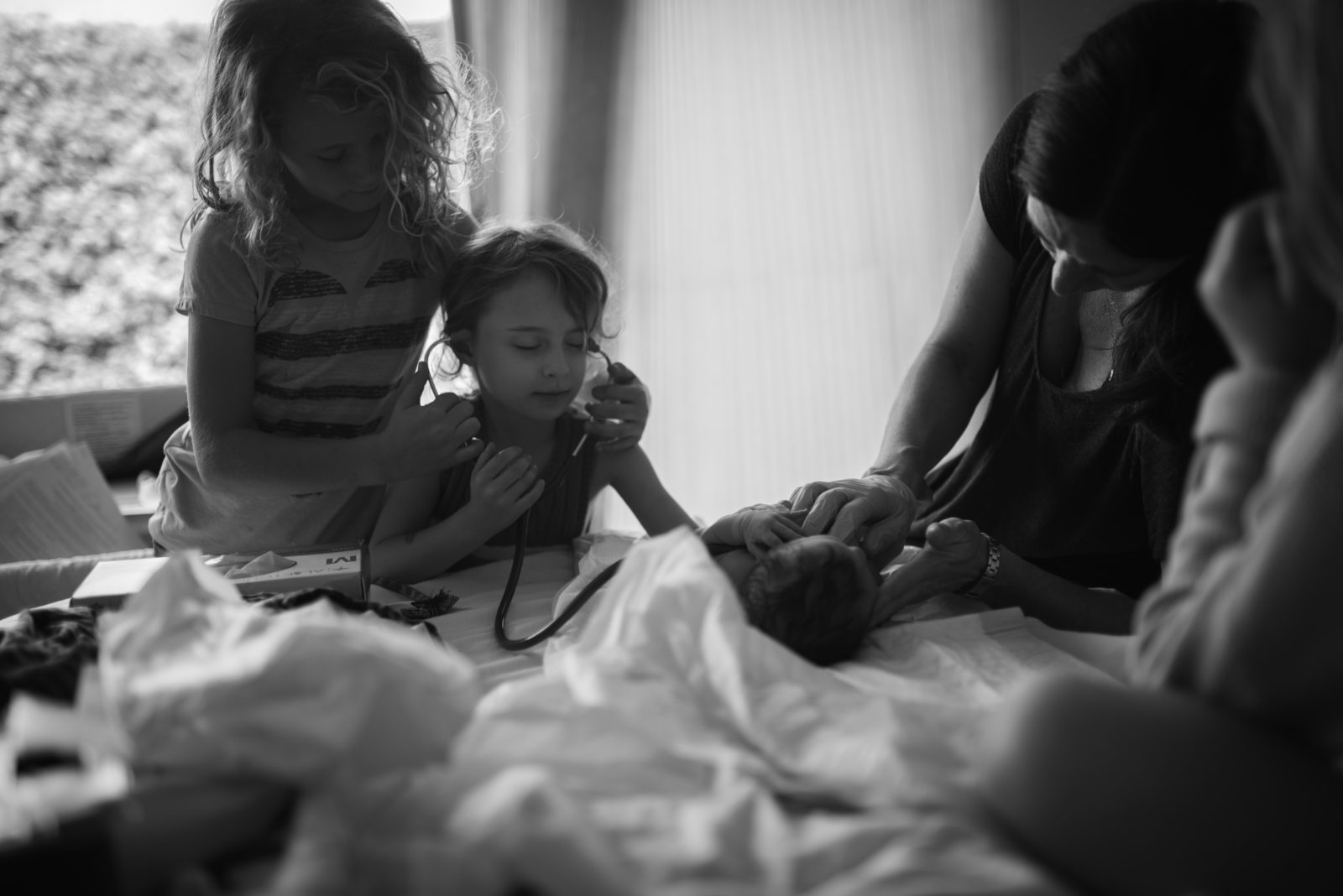 Older sister checks her baby sister's heart with her eyes closed while midwife Monica Wood asses baby right after birth photographed by ArtShaped Photography and Birth Services.