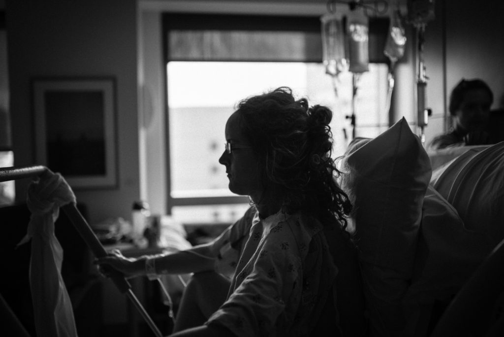 Black white image of mother using the hospital birth bar to push her baby out. Image captured at UCLA Westood by ArtShaped Photography and Birth Services.
