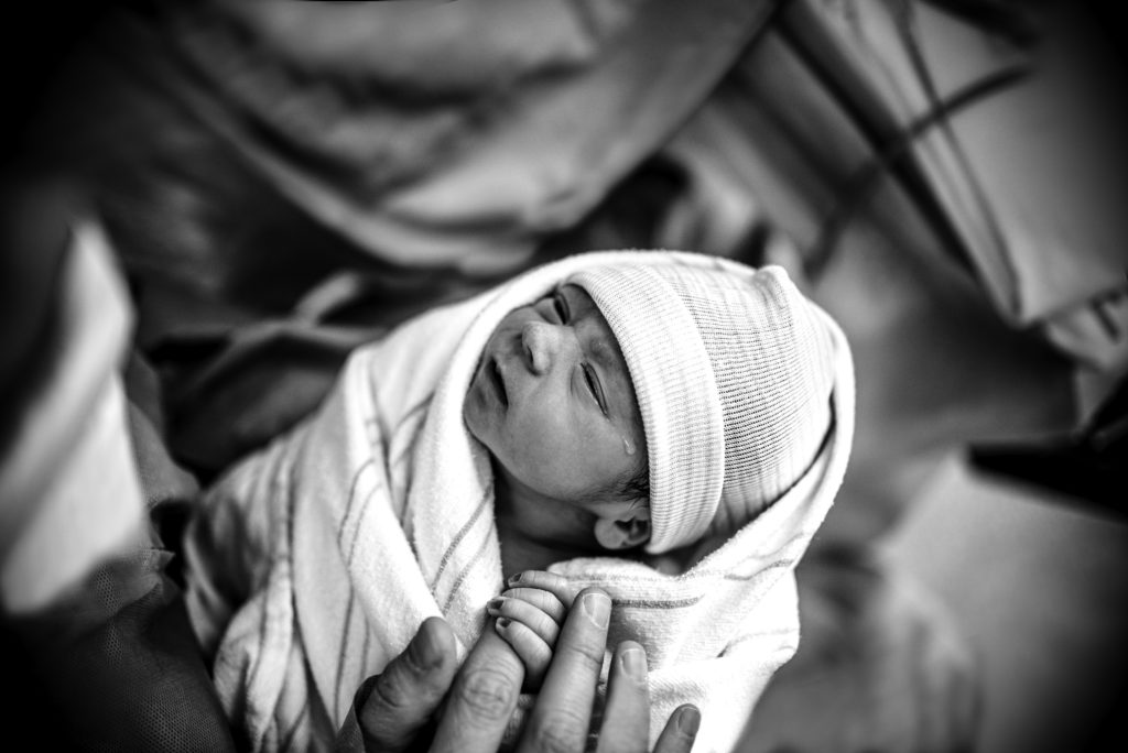 This black and white image is the proof that babies can feel everything since the moment of birth. In this picture by ArtShaped Photography and Birth Services we witness baby shedding a tear as he looks at his daddy for the first time.
