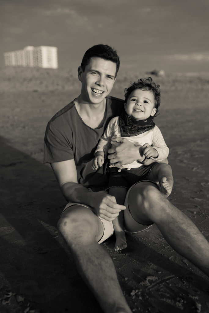 Black and white image of  afather sitting on the sand at the Santa Monica Beach while holding his toddler son during a family portrait session with ArtShaped Photography and Birth Services