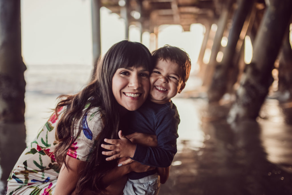 Color image of mom wearing a flower dress and hugging cheek to cheek her son. Both smiling under the Santa Monica Pier for ArtShaped Photography and Birth Services.