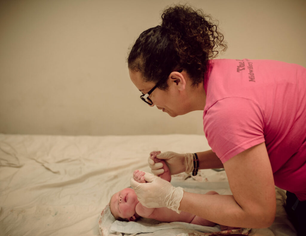 In this color image by ArtShaped Photography and Birth Services we witness a hombirth midwife performing the first pediatric visit on a newborn baby, just born at home in Los Angeles CA