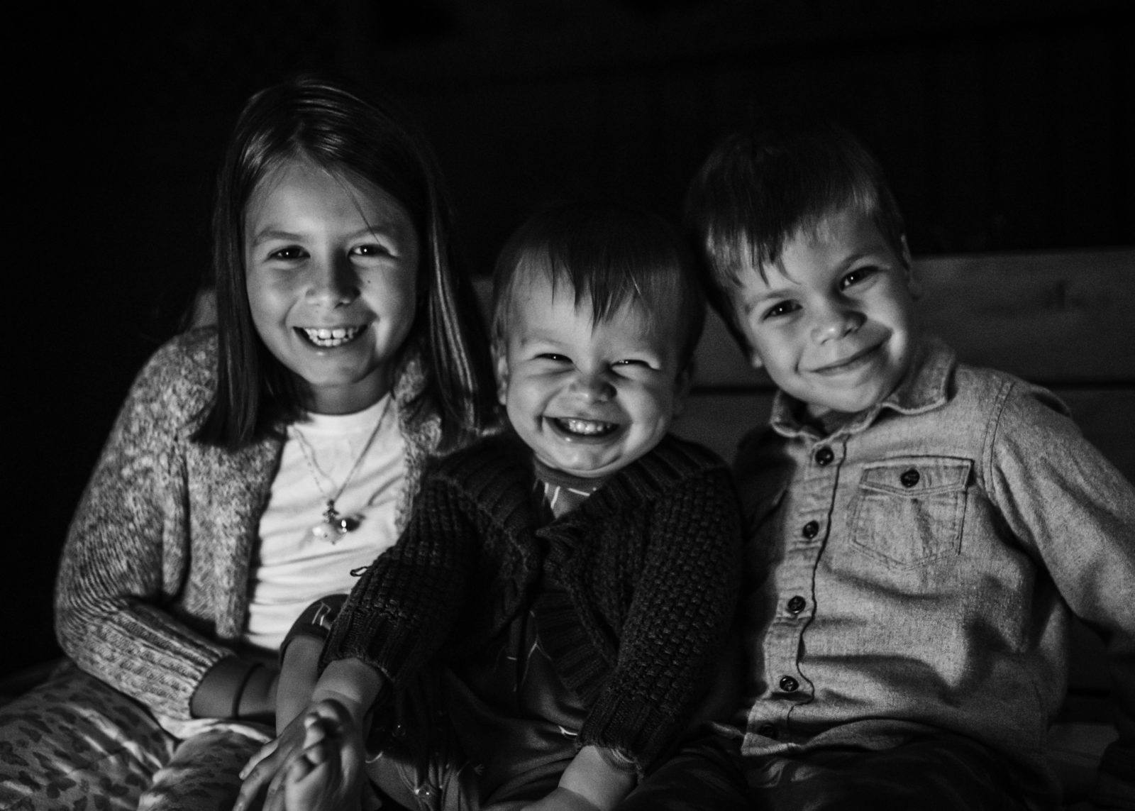 Black and white image of three children smiling at the camera captured in Los Angeles by ArtShaped Photography and Birth Services