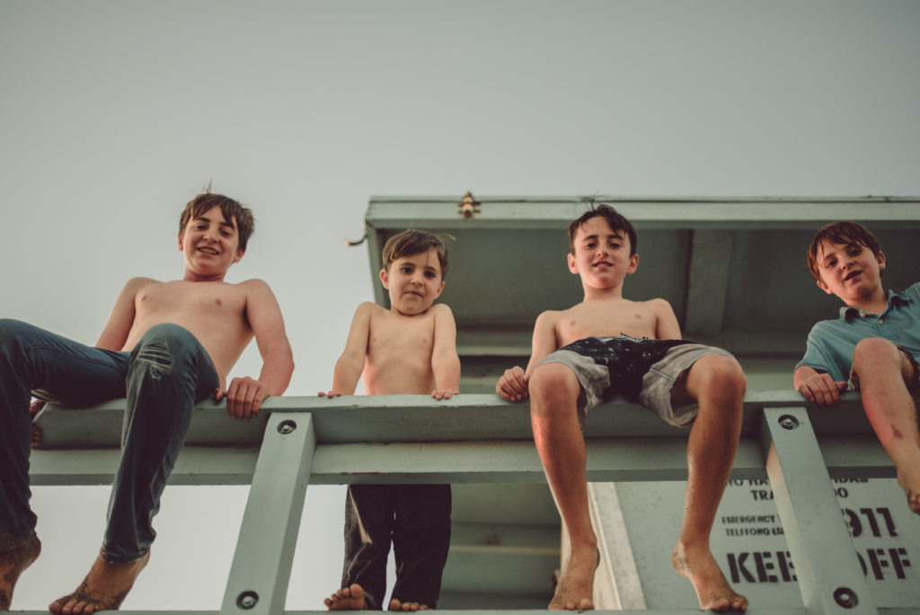 Bottom-up view of four borthers looking down at the camera of ArtShaped Photography and Birth Services while sitting on the lifeguard tower in Santa Monica, California.