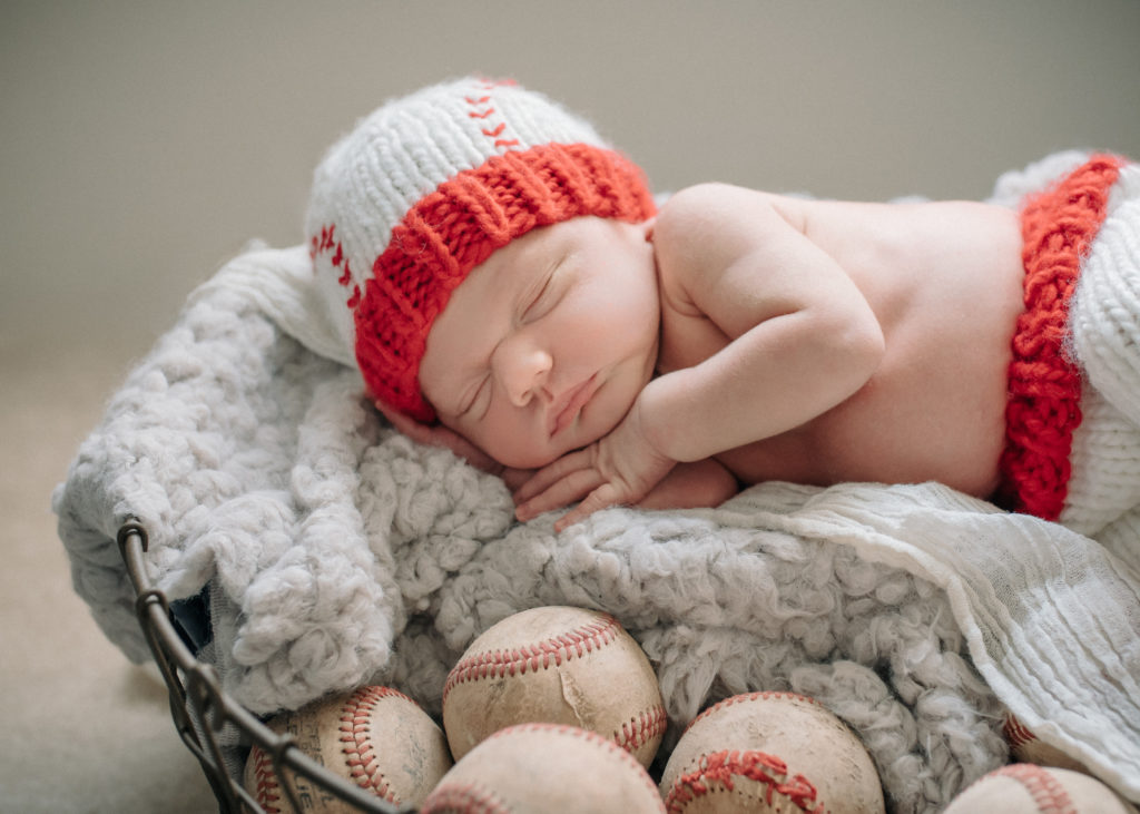 In this color image by ArtShaped Photography a newborn baby sleeps on his side on a cosy blanket and surrounded by baseballs.