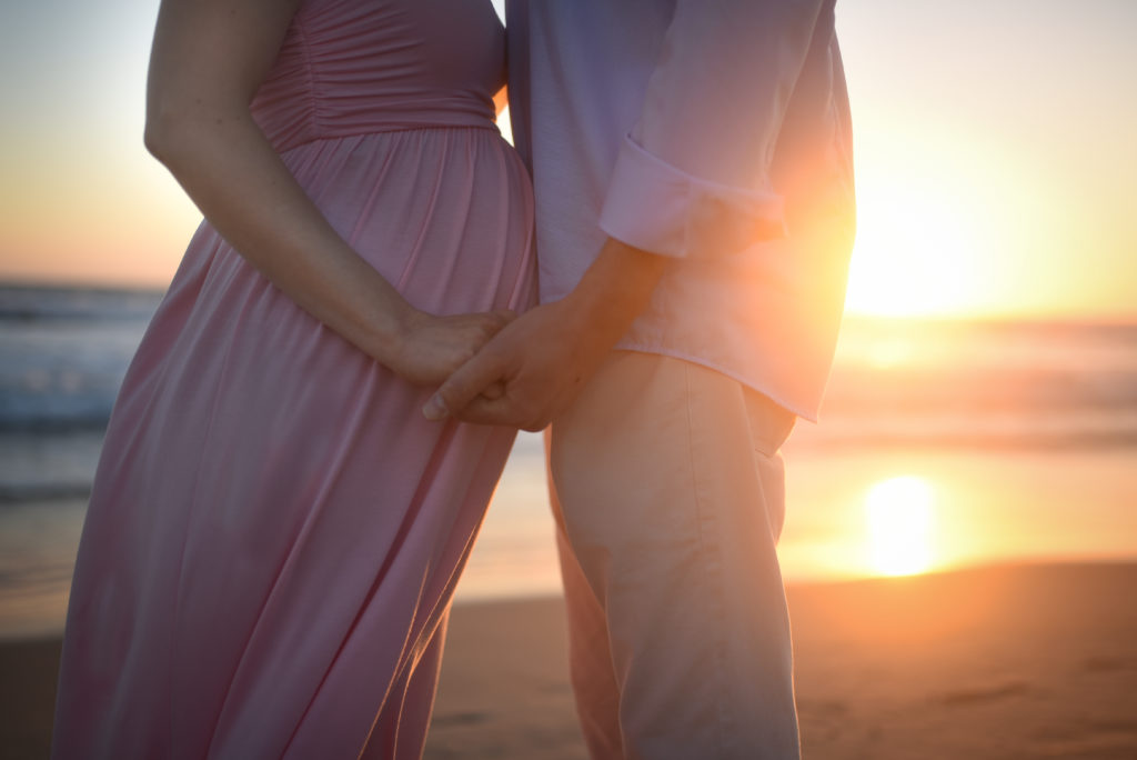 Pregnant couple hold hands in front of the sunset during their maternity photography session with ArtShaped Photography and Birth Services