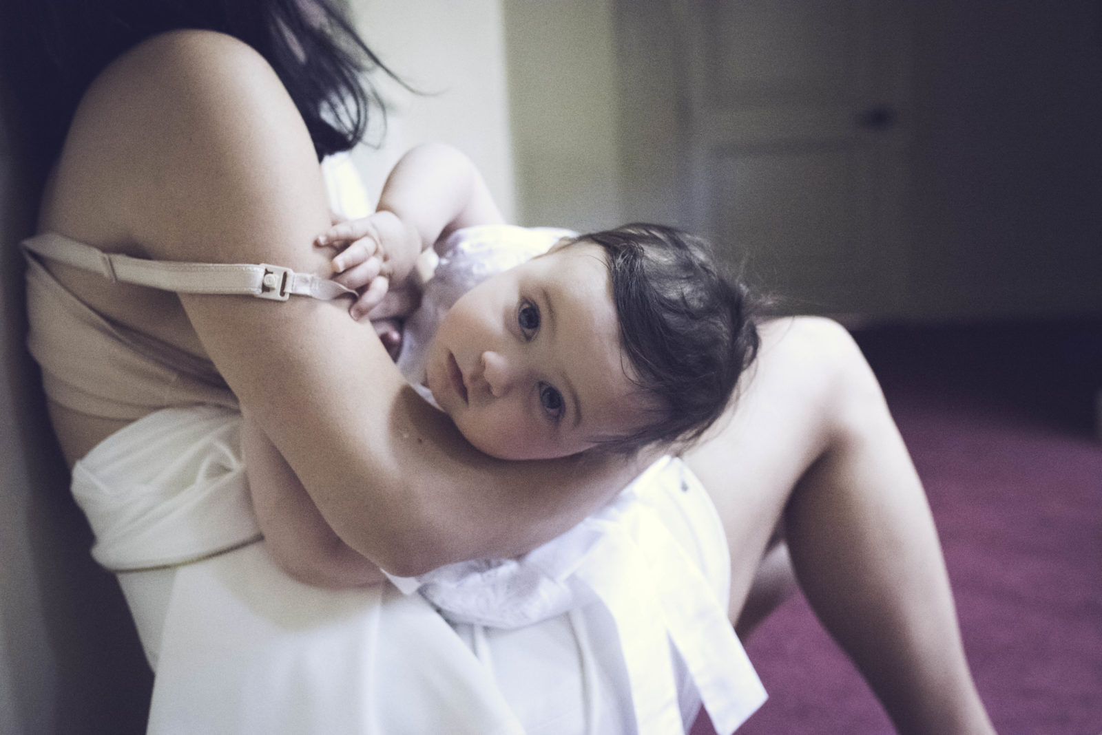 Color image by ArtShaped Photography and Birth Services of little girl looking at the camera and taking a break from nursing.
