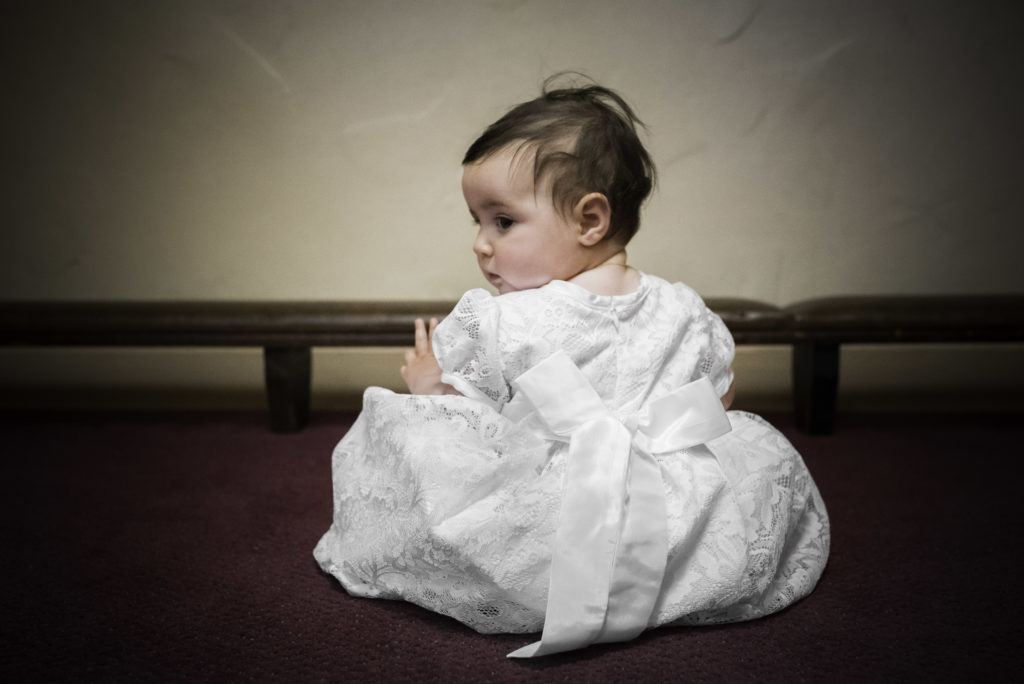 Color portrait of toddler girl during her baptsim photographed by ArtShaped Photography and Birth Services.