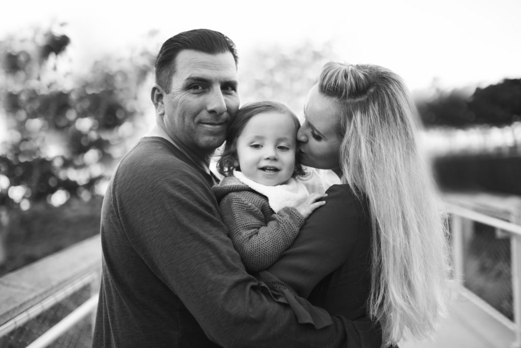 Black and white image curtesy of ArtShaped Photography and Birth Services of family of three posing at the park in Santa Monica during their family portrait session.