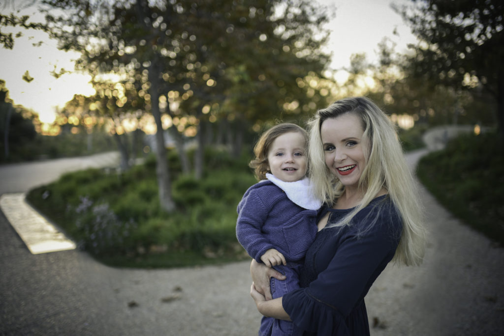 Photo session at sunset in the park with ArtShaped Photography and Birth Services where mom holds her toddler son on her hip and they both smile at the camera.