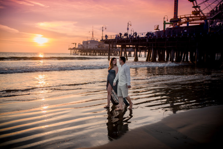 Beautiful first time mom walks gracefully with her husband, feet in the water by the Santa Monica Pier as the sun sets on a warm November afternoon. Maternity photo session by ArtShaped Photography and Birth Services