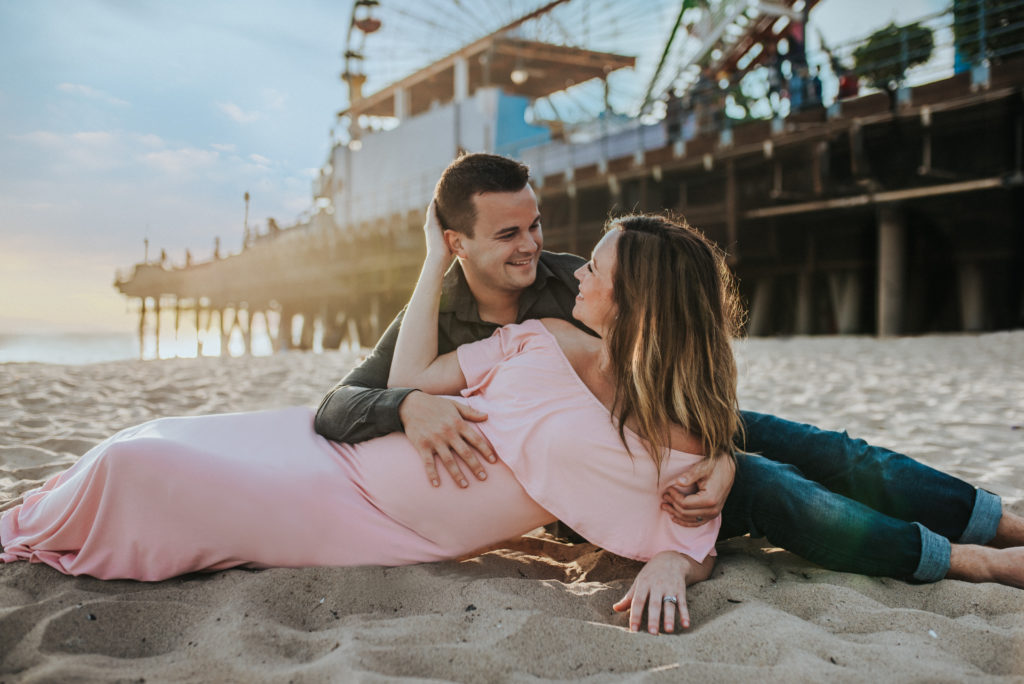 Future mom and dad cuddle on the sand beneath the Santa Monica Pier with ArtShaped Photography and Birth Services