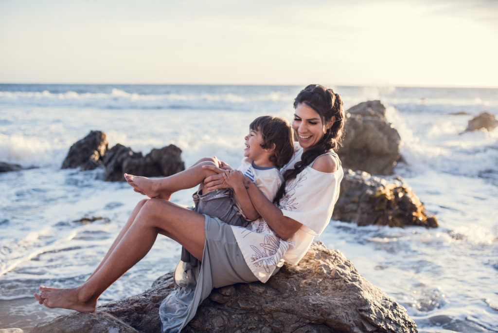 Mother and son sitting on a rock at El MAtador Stae Beach during their family session with ArtShaped Photography and Birth Services