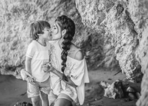 Black and white photograph of mother and child kissing in front of the rocks at El Matador State Beach, immortalized by photographer Diana Hinek for ArtShaped Photography and Birth Services.