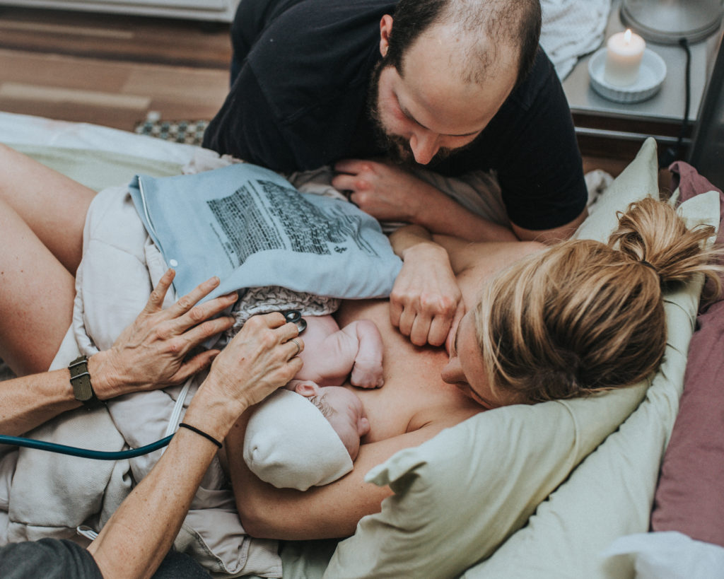 Top view image of hands of midwife checking baby's vitals while he is skin-to-skin with mom and looked over by dad. Image captured by ArtShaped Photography and Birth Services