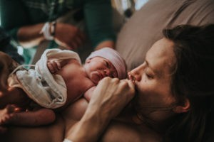 Color image of mother and baby right after birth where mother kisses her baby's hand during a very emotional first look. Image courtesy of ArtShaped Photography and Birth Services