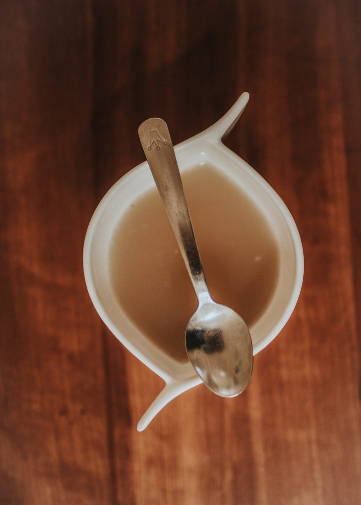 Top view of white cup with bone broth and a silver spoon on balanced on top.