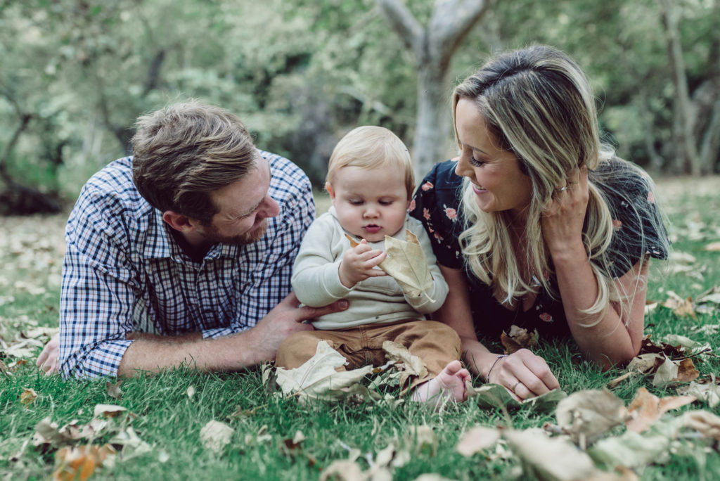 Mom and Dad look at baby while playing in the grass in Tamescal Canyon