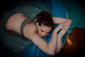 color-image-pregnant-woman-leaning-on-an-inflatable-blue-pool-wearing-a-teal-bralette. Turquoise-towel-on-the-floor.
