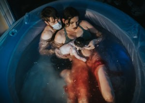 Color image of woman checking out her newborn baby as she peels off the amniotic sac from her body. Man wearing a surgical mask holds her and her baby born almost en-caul. they are all in the birth tub filled up with water and blood streaming.