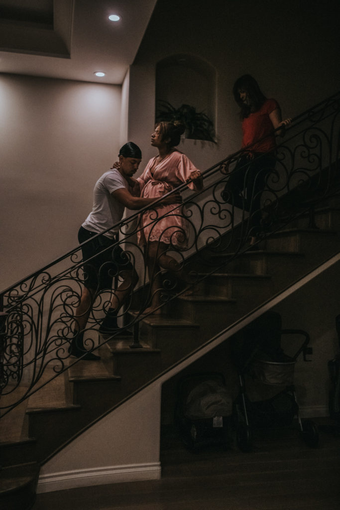 Couple laboring on the stairs in the dark captured by Los Angeles Birth photography ArtShaped Photography