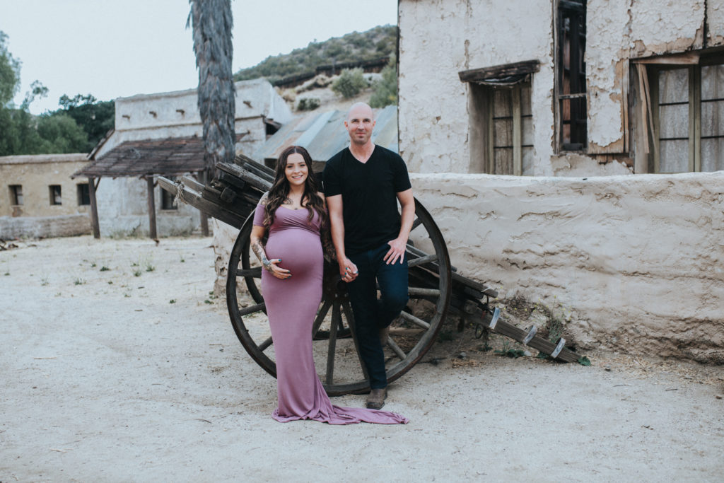 Color image of couple standing in front of am old broken wheel carriage and adobe house. They hold hands and look stright at the camera. Woman is pregnant and wearing a teal colored dress. Partner is dressed in dark and has his hand in his pocket.